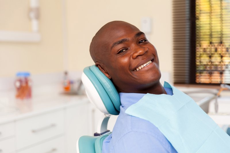 A young man sitting back in the dentist's chair in preparation for his six-month checkup and cleaning