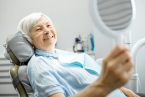 gray-haired woman admiring her smile in the mirror