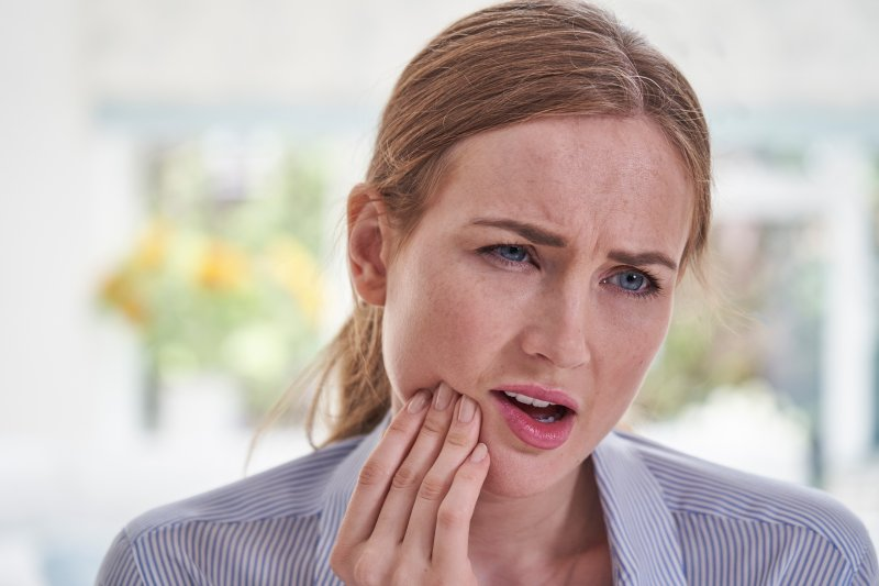 Young woman rubbing her jaw in concern